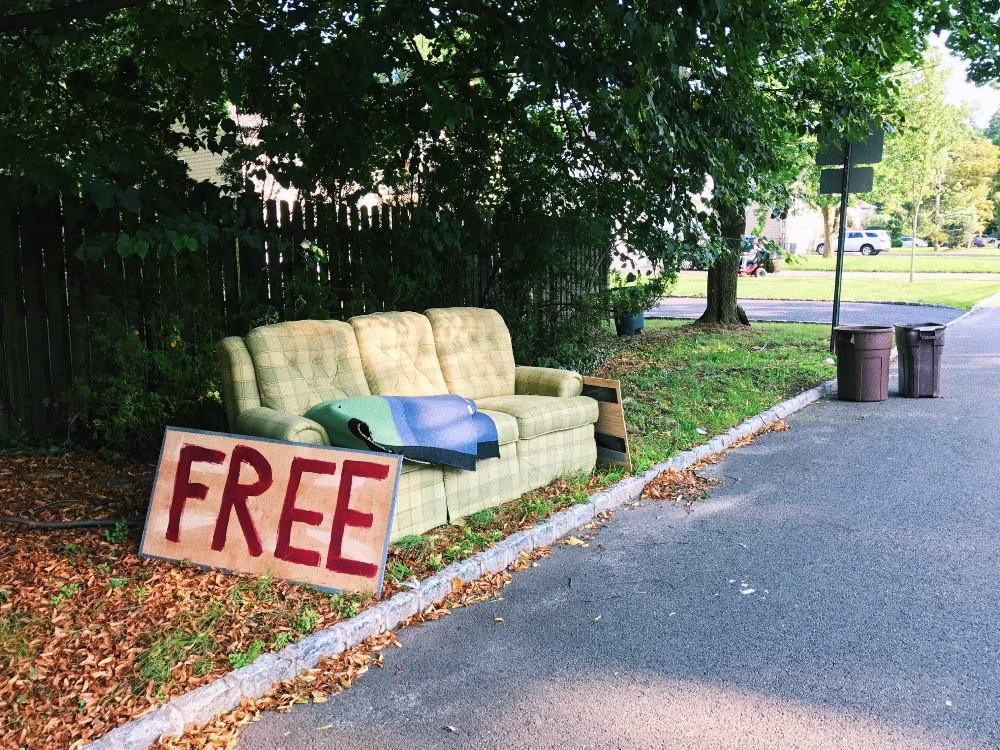 "Photo of discarded couch with sign that says ""Free"""
