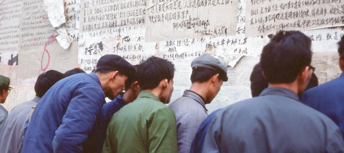 Photo of men looking at wall of writing