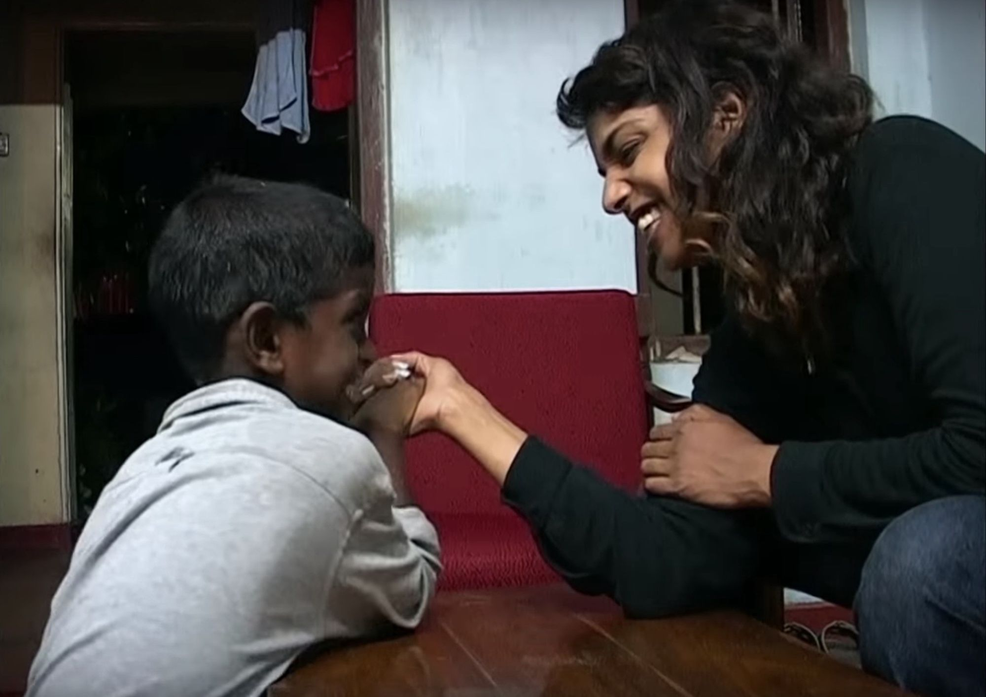 Photo of M.I.A. smiling with a boy in Sri Lanka