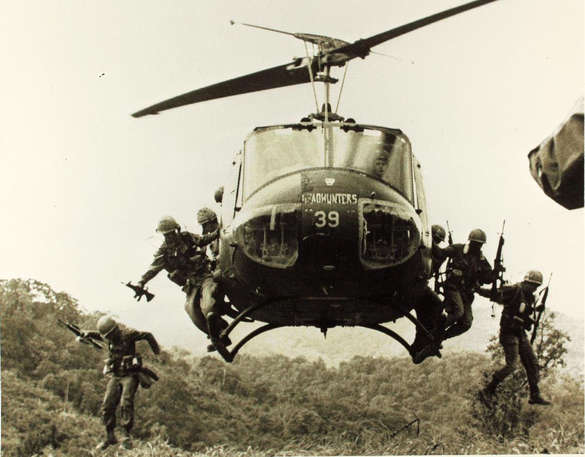 A photograph depicting soliders in a helicopter during the Vietnam War